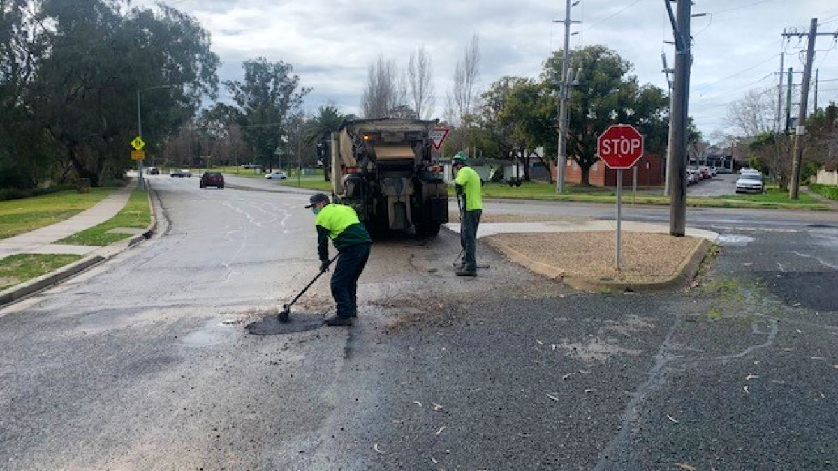 Two men in safety shirts behind truck, filling in potholes