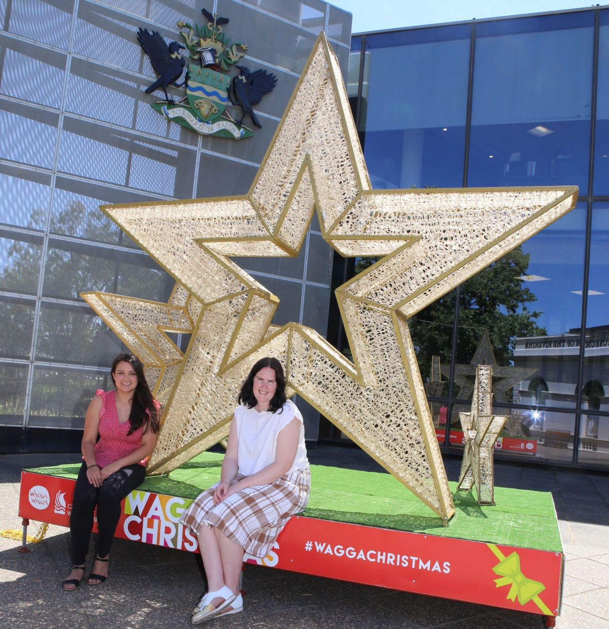 Two women sit in front of a large star